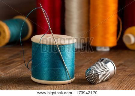 Spool Of Blue Thread, A Needle, And A Thimble