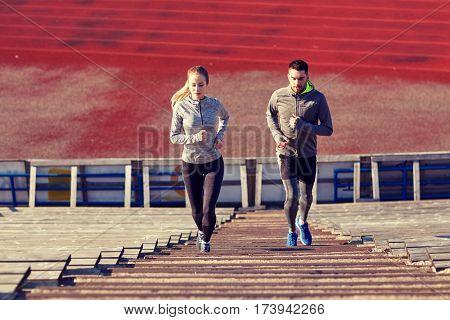 fitness, sport, exercising and lifestyle concept - couple running upstairs on stadium