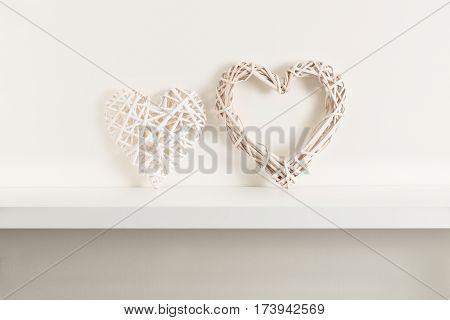 A pair of wicker hearts on white shelving