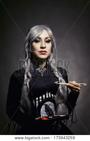 Renaissance girl posing with sushi over grey background
