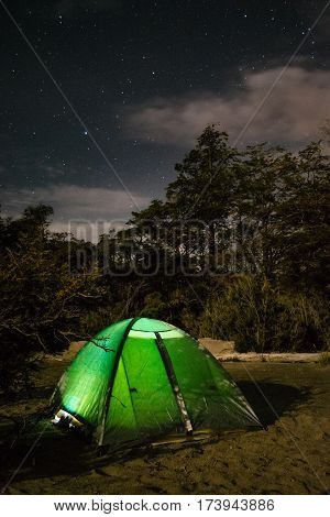 Night camping in Patagonia / Green tent on a beach at midnight