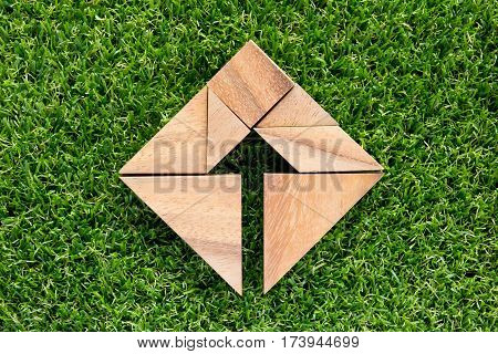 Wooden tangram puzzle as arrow in square shape on green grass background (Concept for business direction and decision)
