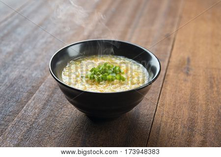 Asian style congee bowl on wooden table background.