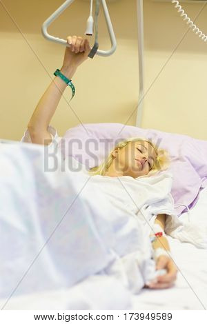 Bedridden female patient lying in hospital bed, recovering after surgery.
