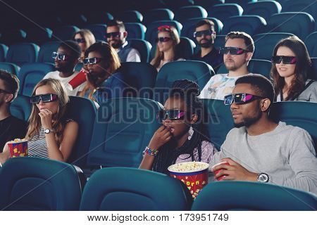Group of africans and caucasians watching movie in 3d glasses in modern cinema hall. Young people eating popcorn and drinking cola, spending free time in cinema.