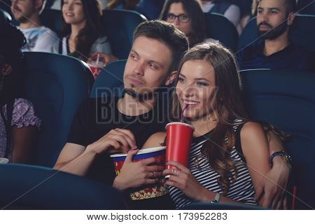 Two friends embracing and sitting in modern cinema hall, watching funny movie. Positive couple of caucasian spending free time in cinema drinking cola and eating popcorn.