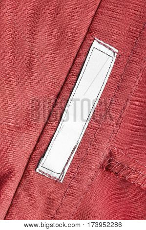 Blank white clothes label on red cotton as a background