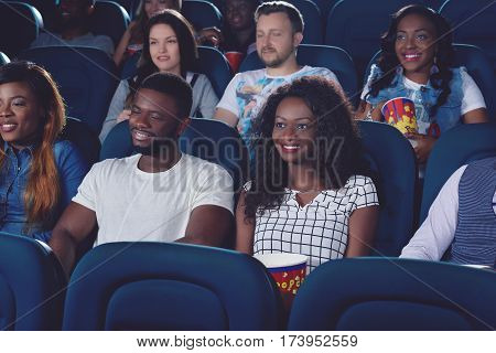 African girls and boy spending free time together in cinema hall and happy smiling. Friends sitting in comfortable chairs and  watching movie in modern cinema hall.