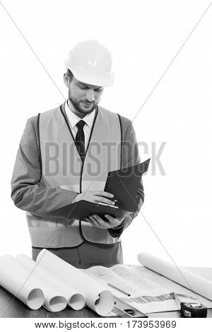 Building industry pro. Monochrome studio shot of a businessman builder in a protective helmet and safety vest working on his building plans making notes on clipboard architect worker engineer concept