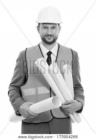 Business developer. Vertical monochrome shot of a businessman architect in a safety vest and hardhat smiling to the camera holding building project blueprints development building construction concept