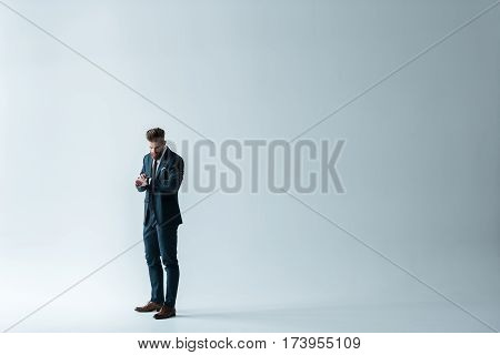 Full length view of stylish businessman checking wristwatch on grey