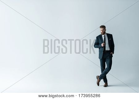 Full length view of handsome bearded businessman in stylish suit posing on grey