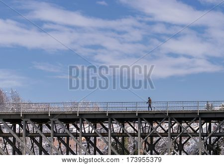 Novo mesto Slovenia EU - January 14 2017: A person is taking a walk over a metal bridge and it's heading to the town center.
