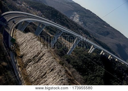 Tall highway road bridge with driving vehicles on it.