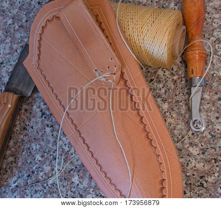 A hand tooled leather knife sheath in process of being crafted in the leather workers workshop using waxed thread for hand stitching