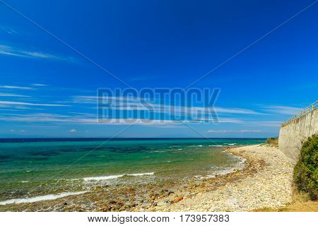 The Rocky Coast With  Tree Overlooking The Turquoise Blue Sea In Warm Summer Day.