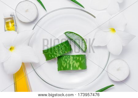 Fresh aloe vera slices with leaf flowers candels and oil on white background