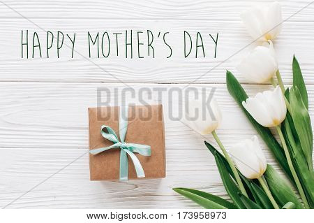 Happy Mothers Day Text Sign On Stylish Craft Present Box And Tulips On White Wooden Rustic Backgroun