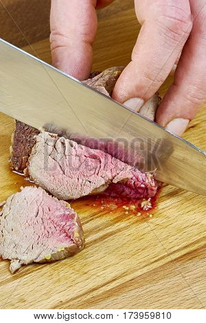 Chef cuts grilled meat on the board with a full series of blood recipe cooking Food being prepared and cooked in a contemporary kitchen, with and without the chef