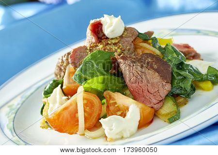 meat salad with green tomatoes on the plate blue background lot of food recipes Food being prepared and cooked in a contemporary kitchen, with and without the chef