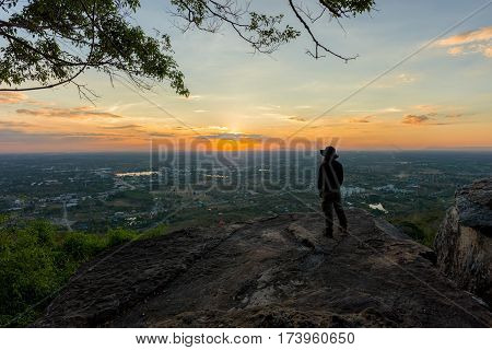 Young man traveler on cliff with beautiful landscape sunset over cliff and city