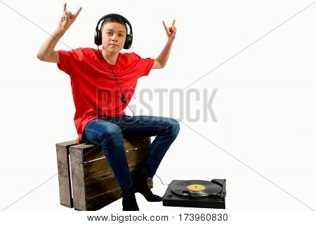 Teenage boy sitting on a crate listening to a LP
