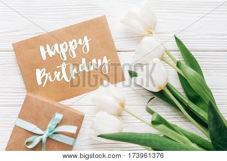 Happy Birthday Text Sign On Stylish Craft Present With Greeting Card And Tulips On White Wooden Rust