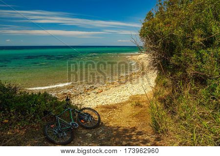 The Rocky Coast  With The Bike Under Tree Overlooking The Turquoise Blue Sea In Warm Summer Day.