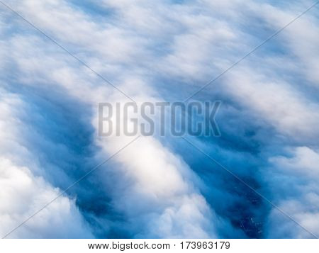 An aerial view of a layer of stratocumulus clouds top-down perspective with a city underneath the clouds. Travel and nature concept.
