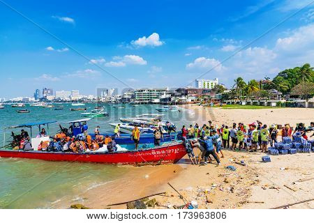 PATTAYA THAILAND - JANUARY 25: Workers loading crates of drinks onto a boat on a beach in Pattaya on January 25 2017 in Pattaya