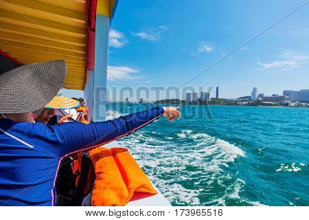 PATTAYA THAILAND - JANUARY 19: This is a traveller pointing to Pattaya city from a boat on its way to another island nearby on January 19 2017 in Pattaya