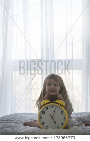 Portrait of aboradle baby girl on the huge alarm clock, isolated in front of the window over white