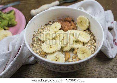 White ceramic bowl of muesli in milk with banana slices close-up view with white towel on wooden table