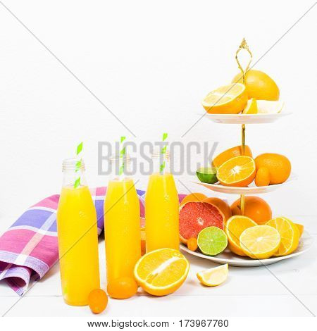 Citrus lemonade in the bottles with fruit ingredients (orange lemon lime grapefruit kumquat) on the cake stand on the white wooden table with copy space