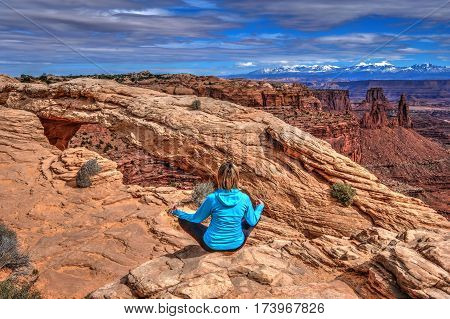 Young woman meditating at cliff by Mesa Arch. Canyonlands National Park. Moab. Utah. United States.