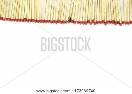 Row of matches with one burnt match on white background .