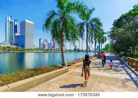 BANGKOK THAILAND - FEBRUARY 01: People walking along the lakeside walking path in Benjakitti park which is a famous park in downtown Bangkok on February 01 2017 in Bangkok