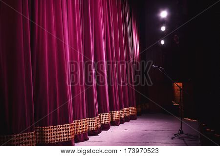 Ready for performance closed stage with big decorative curtain microphone on stand in front of it and big lighting equipment in corner.