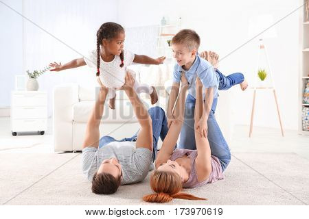 Happy interracial family playing on floor