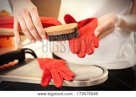 Dry cleaning business concept. Woman working with glove and brush