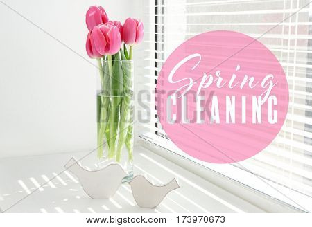 Spring cleaning concept. Tulips in vase on window sill