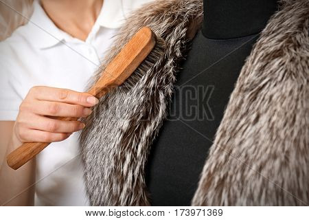 Dry cleaning business concept. Woman working with fur coat and brush