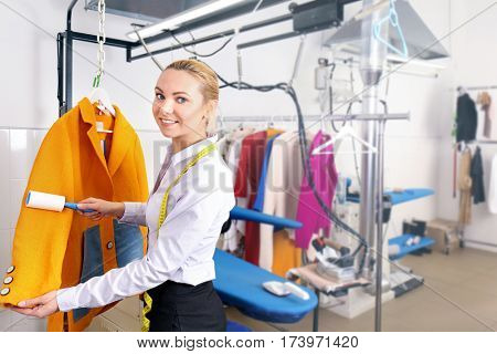 Dry cleaning business concept. Woman working with coat and adhesive roller