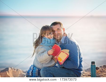 Father reading a book to his daughter outdoors