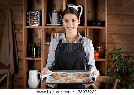 Young woman in apron holding baking tray with cookies on kitchen