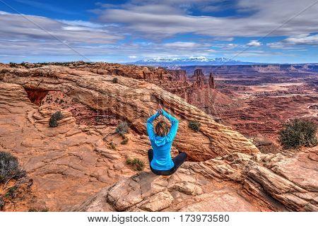 Young woman meditating at cliff by Mesa Arch. Canyonlands National Park. Moab. Utah. United States.