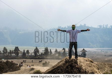 Traveler standing and  extend the arms at Bromo Mountain, Tengger Semeru national park, East Java, Indonesia.