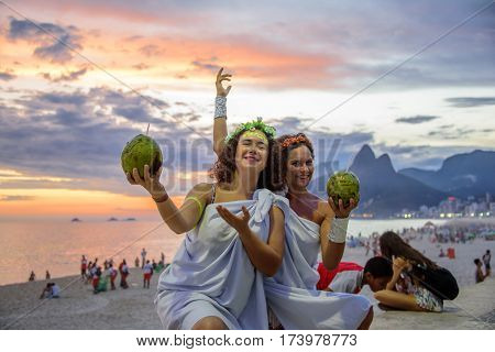 RIO DE JANEIRO, BRAZIL - FEBRUARY 27, 2017: Two women in the costumes of Greek Goddesses wearing flowers diadems and holding coconuts on the background of the beautiful sundown at Ipanema beach