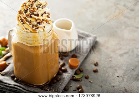 Caramel iced latte with whipped cream and syrup on light background