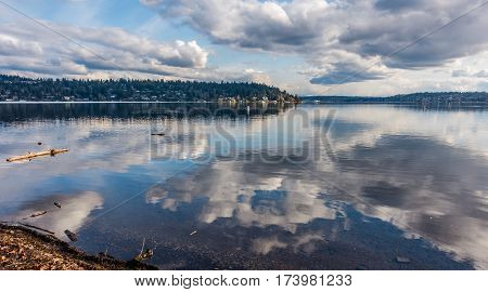 Billowing clouds are reflected on the surface of Lake Washington. Photo taken at Seward Park.